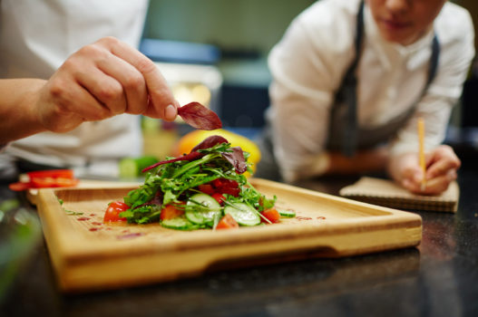 Chef putting leaf of basil on top of vegetable salad