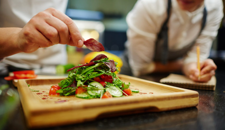 Chef putting leaf of basil on top of vegetable salad